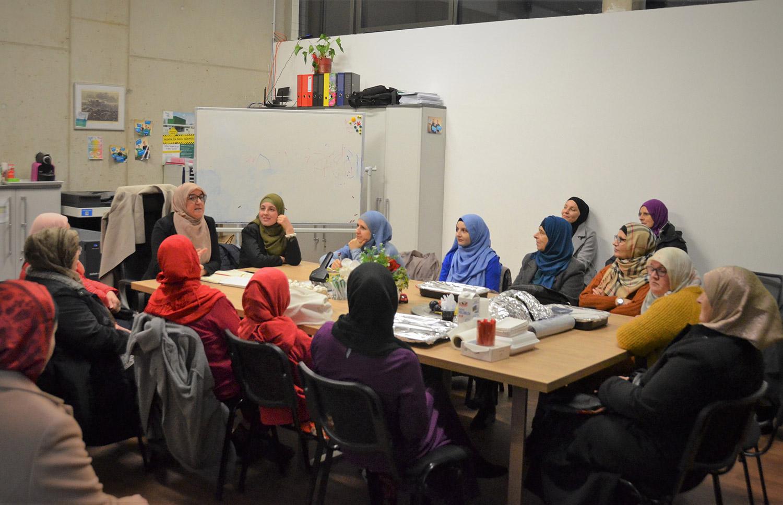 Frauen mit Kopftuch sitzen an einem Tisch und unterhalten sich