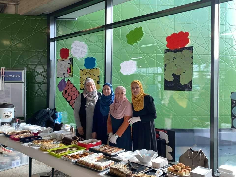 Frauen mit Kopftuch hinter einem Tisch mit viel Kuchen